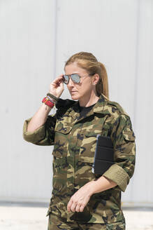 Confident mature blond female army soldier wearing sunglasses at military base on sunny day - MTBF00680