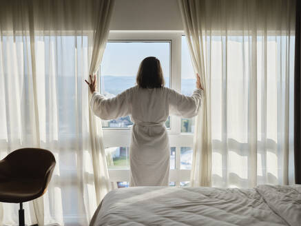 Woman opening white curtain while looking through window at luxury hotel room - ZEDF03901