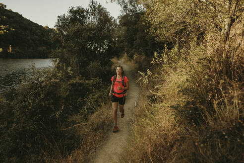 Smiling woman running on footpath at Sierra De Hornachuelos, Cordoba, Spain - DMGF00168