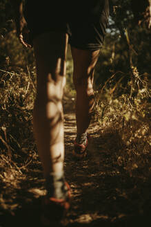 Female trekker walking on narrow path at Sierra De Hornachuelos, Cordoba, Spain - DMGF00174