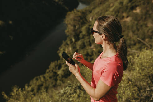 Woman using mobile phone while standing on mountain at Sierra De Hornachuelos, Cordoba, Spain - DMGF00180