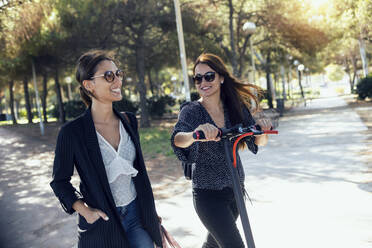 Friends walking with push scooter on road in city - JSRF01151
