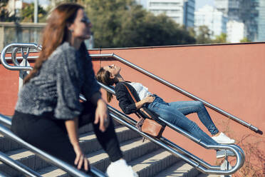 Women relaxing on railing of staircase in city - JSRF01163