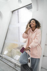 Smiling young woman talking on smart phone while standing at airport - SNF00592