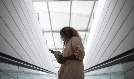 Young woman text messaging on smart phone while wearing protective face mask - SNF00595