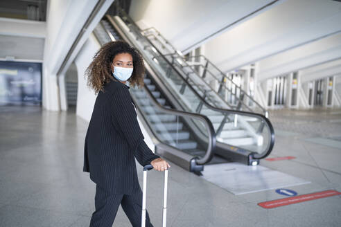 Young woman looking over shoulder while standing at airport - SNF00601