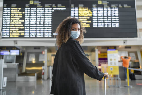 Woman wearing protective face mask looking over shoulder while standing at airport - SNF00604