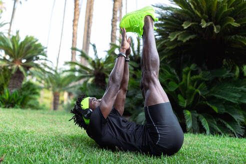 Young African American sportsman in stylish activewear sitting on green grass and doing stretching exercises after running in park - ADSF16176