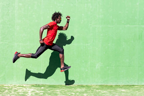 Side view of black sportsman in activewear in moment of jumping during intense workout on sunny day - ADSF16182