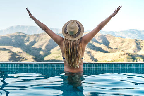 Back view of unrecognizable slim female in swimwear and hat outstretching arms in swimming pool and admiring mountainous landscape during summer vacation - ADSF16383