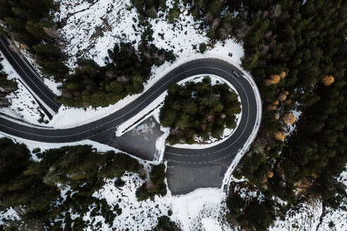 Spectacular drone view of lonely car on road junction in coniferous woods with snow in winter - ADSF16441