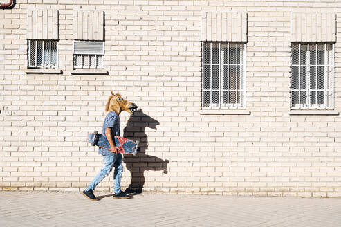 Man walking while holding skateboard wearing horse mask on footpath in city during sunny day - JCMF01539