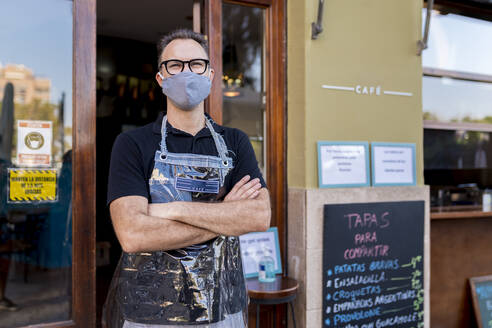 Male owner in face mask standing with arms crossed against cafe during COVID-19 crisis - EGAF00854