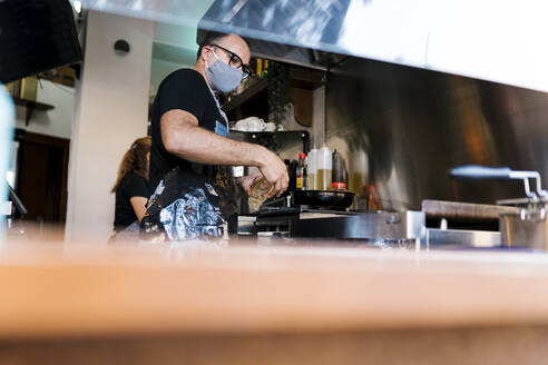 Male barista wearing protective face mask while cooking in kitchen of coffee bar during COVID-19 - EGAF00863