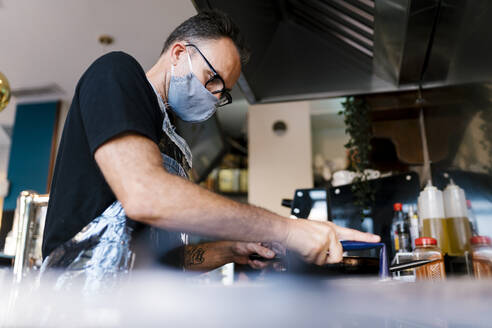 Male barista wearing face mask while cooking in kitchen of coffee shop during COVID-19 crisis - EGAF00866