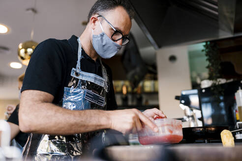Male barista wearing face mask while preparing food in cafe during COVID-19 outbreak - EGAF00872