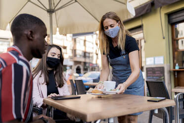 Waitress in face mask serving young couple at cafe during COVID-19 outbreak - EGAF00902