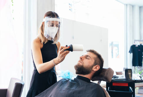 Female barber removing hair with brush after finishing haircut for male customer in bright barbershop - ADSF16542