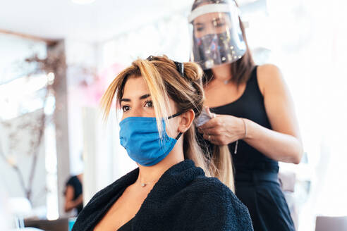 Side view low angle of female hairdresser in face shield and mask making hairdo for customer while working in salon during coronavirus pandemic - ADSF16548
