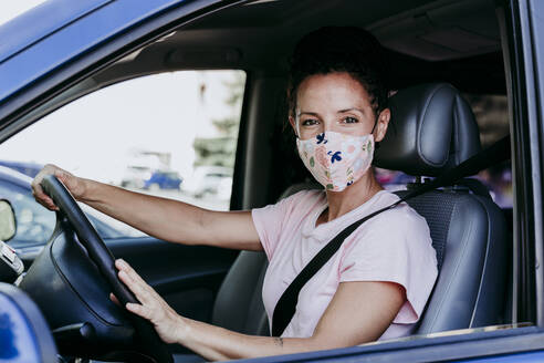 Mid adult woman wearing protective mask while sitting in car - EBBF00791