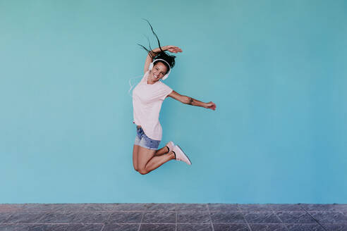 Cheerful woman jumping while listening music through headphones against turquoise wall - EBBF00803