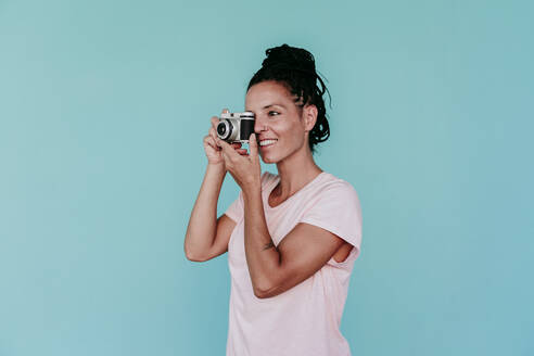 Smiling woman photographing with old-fashioned camera against turquoise background - EBBF00812