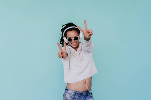 Happy fashionable woman showing peace sign while listening music through headphones against turquoise background - EBBF00818