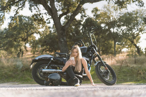 Blond female biker using smart phone while sitting against motorcycle on roadside - DAMF00522