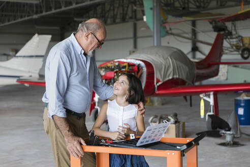 Grandfather and granddaughter looking at each other while standing in airplane hangar - EIF00191