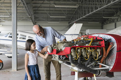 Grandfather showing how to fix airplane tool to granddaughter - EIF00194