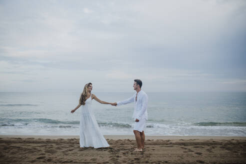 Couple holding hands while dancing against sea at beach - GMLF00663