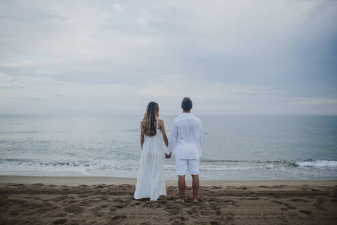 Couple holding hands while admiring sea view standing at beach - GMLF00672