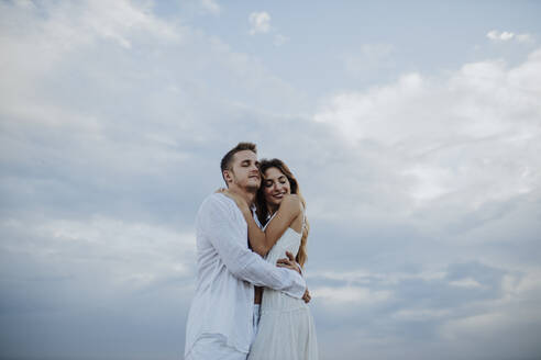 Couple embracing each other while standing against sky - GMLF00684
