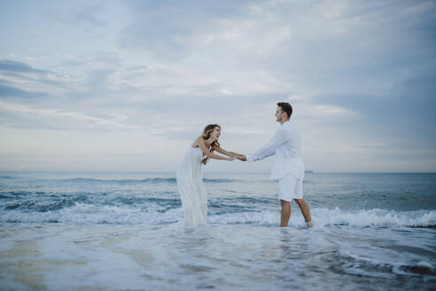 Playful couple holding hands while standing in water at beach - GMLF00690