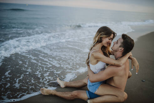Young couple doing romance while sitting on beach - GMLF00693