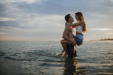 Man carrying woman while standing in water during sunset at beach - GMLF00702