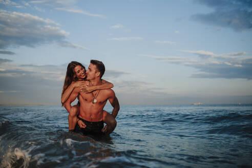 Smiling man piggybacking woman while standing in water at beach - GMLF00705