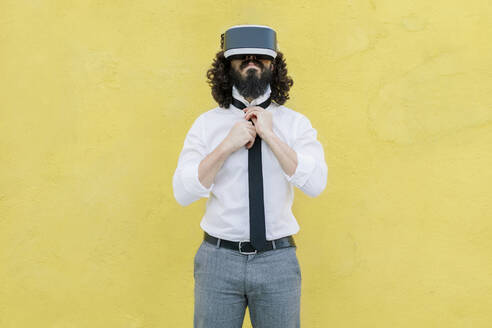 Businessman wearing virtual reality eyeglasses tying tie while standing against yellow wall - MRRF00550