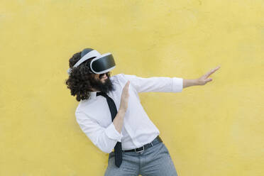 Man wearing virtual reality eyeglasses gesturing stop sign while standing against wall - MRRF00556