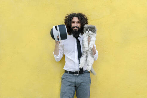 Man holding virtual reality eyeglasses and cat while standing against wall - MRRF00559