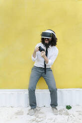 Businessman wearing virtual reality eyeglasses playing video game while standing against wall - MRRF00562
