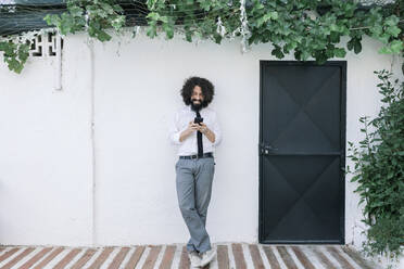 Businessman using mobile phone while standing against wall - MRRF00565