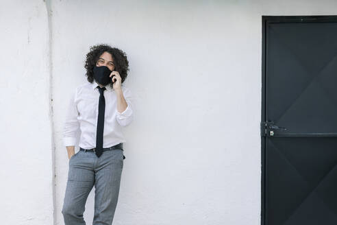 Businessman with face mask talking on mobile phone while standing against wall - MRRF00568