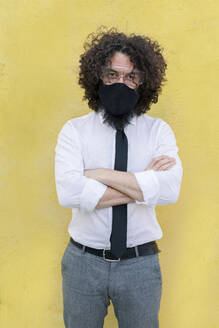 Businessman wearing face mask and eyeglasses standing with arms crossed against wall - MRRF00571