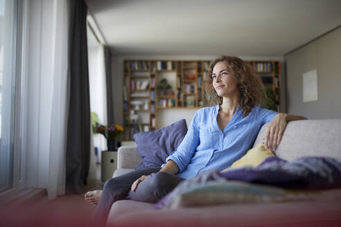 Thoughtful woman smiling while sitting on sofa at home - RBF07943