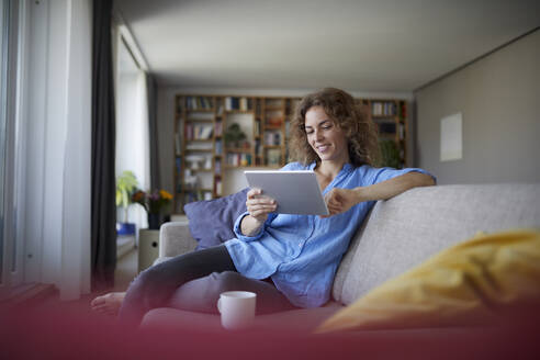 Woman using digital tablet while sitting on sofa at home - RBF07949