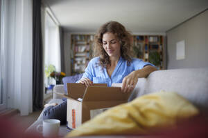 Woman opening box while sitting on sofa at home - RBF07952