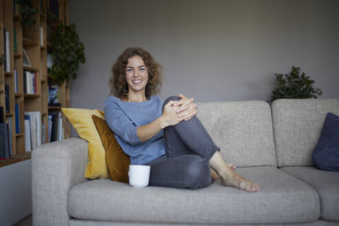 Smiling woman drinking coffee while sitting on sofa at home - RBF07973
