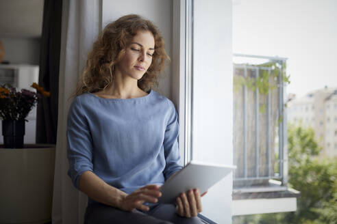 Woman using digital tablet while sitting on window sill at home - RBF07985
