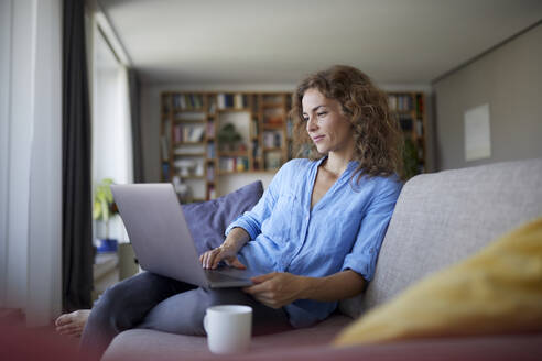 Mid adult woman using laptop while sitting on sofa at home - RBF07997